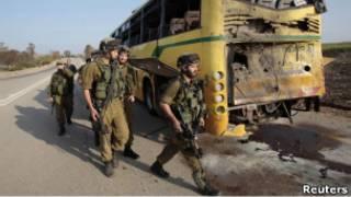 Израильские солдаты рядом с подорванным автобусом