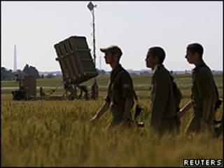 Soldados israelenses passam em frente ao sistema anti mísseis Domo de Ferro no sul do país, em Ashkelon (Reuters)