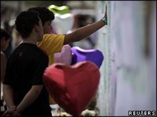 Meninos observam homenagem às vítimas em frente à escola Tasso da Silveira (Reuters)