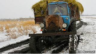 Трактор еде по проселочной дороге