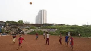 Anak-anak main bola di lahan kosong di Jakarta