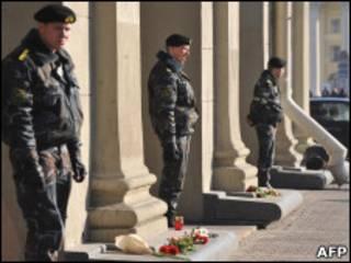 Soldados da Bielorússia do lado de fora do metrô de Minks, diante de coroa de flores