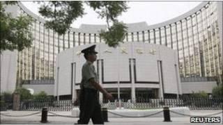Penjaga berjalan melewati Bank Rakyat Cina