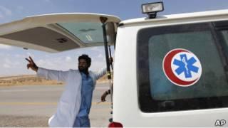 Медик стоит у машины скорой помощи в Ливии
