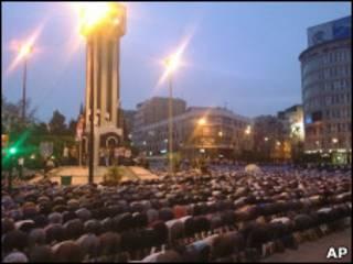 Manifestantes rezam na Praça do Relógio, em Homs