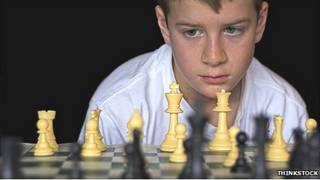 Niño mira tablero de ajedrez