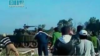 Толпа наблюдает, как человек бросает камень в танк в Дараа