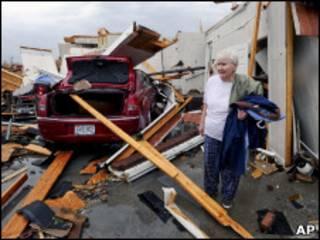 Mulher toma pertences de casa destruída pelo tornado no Alabama