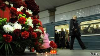 """Цветы и свеча на платформе станции метро """"Парк Культуры"""" в Москве"""