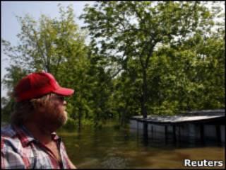 Morador em frente a casa alagada na Louisiana