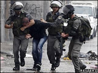 Policial de fronteira israelense prende palestino durante protesto na Cisjordânia, no domingo (Reuters)