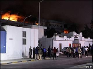 Moradores observam prédios em chamas na madrugada de terça-feira em Trípoli (AFP)