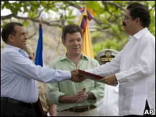Lobo (esq.) e Zelaya durante assinatura do acordo, mediado por Juan Manuel Santos (centro) (AP)
