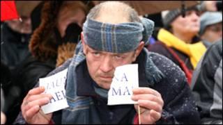 """Латвия: человек разрывает флажок с надписью """"Новый сейм"""""""