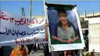 عکسی از حمزه خطیب در دست معترضان