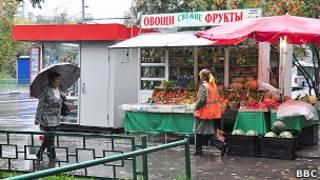 Палатка с овощами и фруктами, мимо которой идут две женщины
