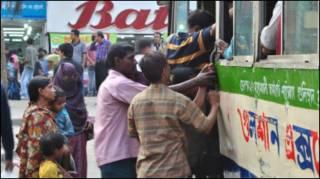 Mulheres tentam embarcar em ônibus em Daca