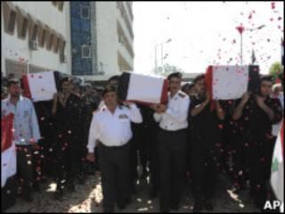 Oficiais de segurança carregam caixões de soldados.