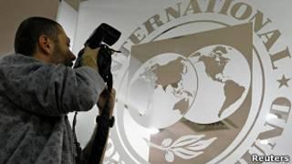 Фотограф рядом с эмблемой МВФ