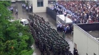 Cảnh sát chống bạo động đang ngăn người dân tràn vào một văn phòng chính quyền của tỉnh Hồ B́ăc