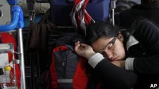 Passageira dorme enquanto espera voo no Aeroparque, em Buenos Aires