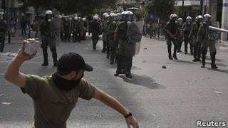 Manifestante a punto de lanzar piedra contra policías en Atenas
