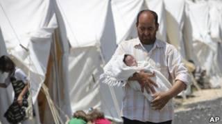 Refugiado carrega bebê em acampamento na cidade turca de Boynuyogun. Foto: AP