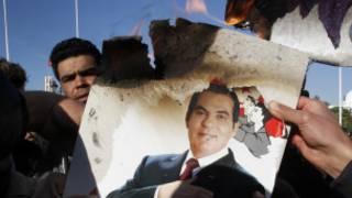 متظاهرون يحرقون صورة لبن علي