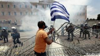Homem carrega bandeira grega em meio a protesto em Atenas. Foto: Reuters
