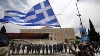 Mulher com máscara contra gás protesta na Praça Sintagma, em Atenas. Foto: Reuters
