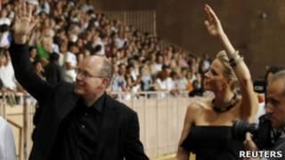 O príncipe Albert II e sua noiva, Charlene Wittstock, acenam para a multdião durante um show da banda The Eagles, no Stade Louis II, em Mônaco, no dia 30 de junho de 2011.