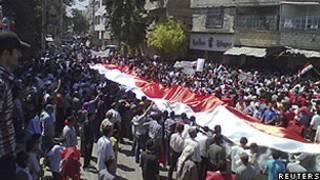 Manifestantes estendem bandeira da Síria em protesto na cidade de Suqba (Reuters)