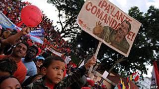 Criança segura cartaz com rosto do presidente Hugo Chávez em manifestação de apoio em Caracas (AFP)