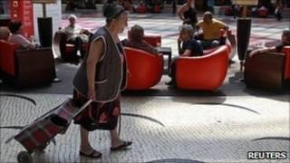 Una mujer arrastrando un carrito de mercado