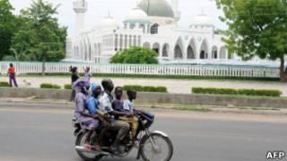 Четыре человека едут на мотоцикле в Майдугури