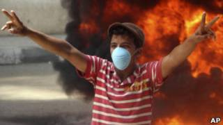 Египетский подросток на фоне пламени во время протестов в Каире