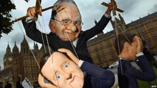 Манифестант в маске Руперта Мердока и с куклой, изображающей Дэвида Кэмерона, в Лондоне