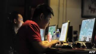 Chineses usam computadores em um café de Pequim.