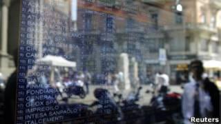 Pedestres passam em frente a tela com cotações de ações da Bolsa de Milão