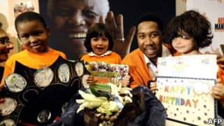 Crianças com cartões posam ao lado do neto de Mandela, Ndaba (Foto: AFP)