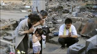 Japanese family praying after March tsunami