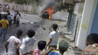 أشخاص يتفرجون على سيارة تحترق بعد أن كانت قد فُخِّخت وتم تفجيرها