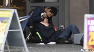 Homem socorre ferida em Oslo. Reuters