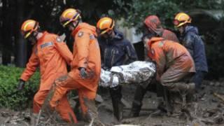 رجال الإسعاف يحملون جثة ضحية انزلاقات كوريا الجنوبية