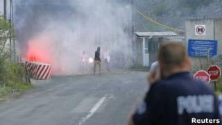 Косовский полицейский наблюдает, как этнические сербы поджигают пост на границе