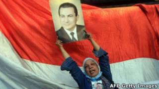 Correligionária exibe cartaz com rosto de Hosni Mubarak (AFP Getty Images)