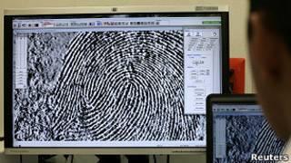 Experto observa huellas dactilares en computadora