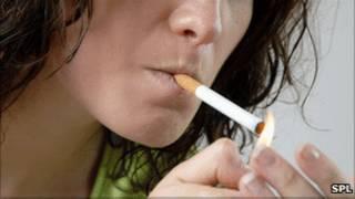 Женщина закуривает сигарету