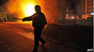 Policial em frente a um edifício em chamas em Croydon, no sul de Londres.