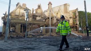 Полицейский на фоне сгоревшего дома